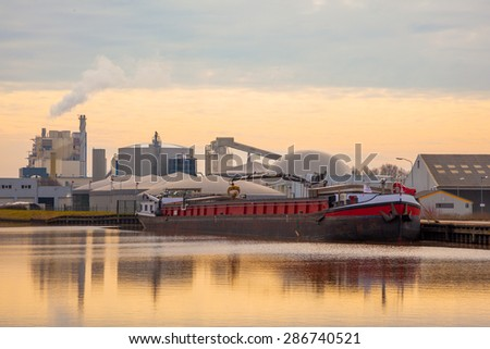 Inland Transportation Barge Unloading at a Chemical Plant - stock photo