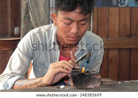 INLE LAKE, MYANMAR, December 15, 2014 : A young man works in a jewel workshop of Inle Lake. Traditional industries products include silk weaving, textiles, carvings and other ornamental objects.