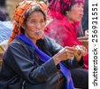 INLE LAKE, MYANMAR - December 01, 2014: an unidentified woman with cigar in traditional dress sells vegetables at market of Inn Dain Khone Village, on Inle Lake. - stock photo