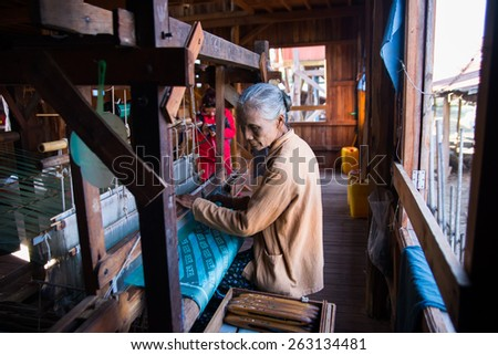 INLE LAKE, MYANMAR, FEB 27: An unidentified Burmese woman weaving clothe from lotus silk on February 27, 2015 in Inle Lake, Myanmar. Silk was produced from lotus is a speciality of Inle Lake area.  - stock photo