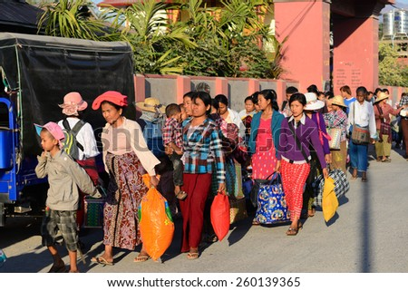 INLE LAKE, MYANMAR - FEB 26: Burmese people on road on February 26, 2015 on Inle Lake, Myanmar. 89% of the Burmese population is Buddhist.  - stock photo