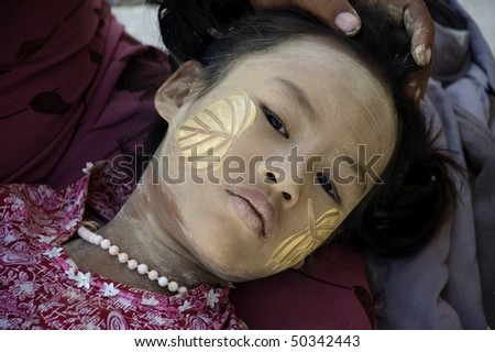 INLE LAKE, MYANMAR - FEB 12: face of the young girl with traditional thanaka on it,  on february 12, 2009 in Inle Lake, Myanmar. - stock photo