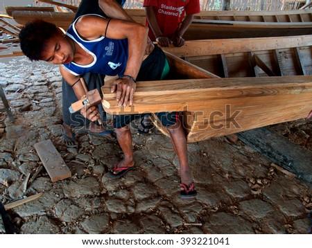 INLE LAKE, MYANMAR - MAR 1, 2015 - Boat builders work in their shop on  Inle Lake,  Myanmar (Burma) - stock photo