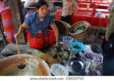 INLE LAKE, MYANMAR - MAR 1, 2015 - Young woman selling freshly cooked food at the weekly market on  Inle Lake,  Myanmar (Burma)
