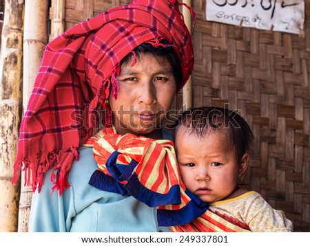 Inle Lake, Myanmar - March 25, 2014: Portrait of unidentified Burmese woman with infant daughter at Indein village, Inle Lake, Shan State, Myanmar.  - stock photo