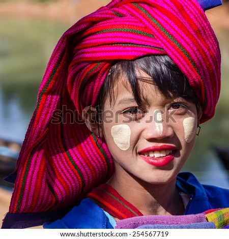 INLE LAKE, MYANMAR - November 30, 2014: an unidentified girl in traditional dress sells textiles crafts at the market of Inn Dain Khone Village on Lake Inle. On the face the traditional makeup Thanaka