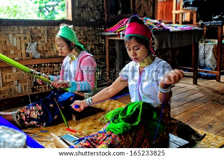 INLE LAKE, MYANMAR, SEPTEMBER 5: Two unidentified Burmese long neck girls weave on September 5, 2013 in Inle Lake, Myanmar. Long neck is a famous ethnic minority group in Myanmar  - stock photo