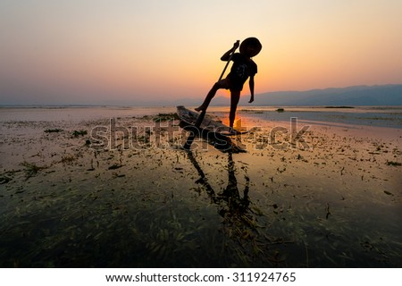 INLE LAKE VILLAGE MYANMAR : Silhouette People rows the wooden boat by his leg in Inle Lake - stock photo