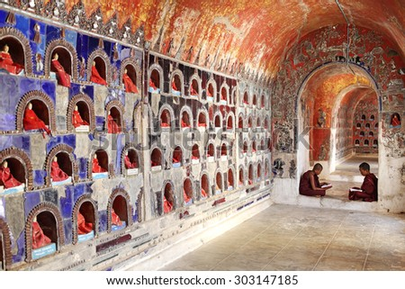 INLE, MYANMAR - DEC 8: Unidentified young novice monks study in Nyan Shwe Kgua temple on Dec 8, 2014 in Inle Lake, Myanmar. Buddhas in alcoves on the wall spectacular of Nyan Shwe Kgua temple - stock photo