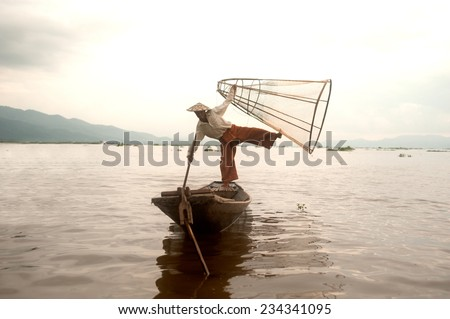 INLE,MYANMAR-SEPTEMBER 29 : Fisherman catches fish for food on September 29,2014 on Inle Lake,Shan state in Myanmar.Intha people possess the leg-rowing style and unique coop-like fishing equipment. - stock photo