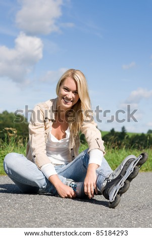 Inline skates young attractive woman wearing jeans sitting asphalt road - stock photo