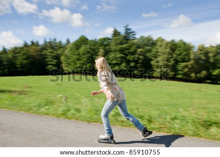 Inline skating young woman speed workout sunny asphalt road - stock photo