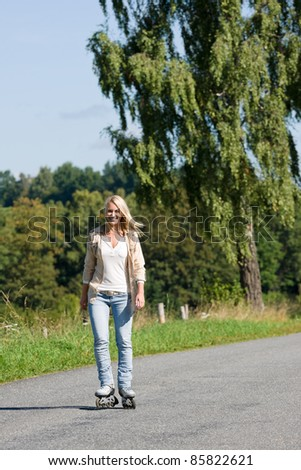 Inline skating young woman wearing jeans on sunny asphalt road - stock photo