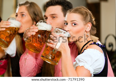 Inn or pub in Bavaria - group of three young people in traditional Tracht drinking beer - stock photo