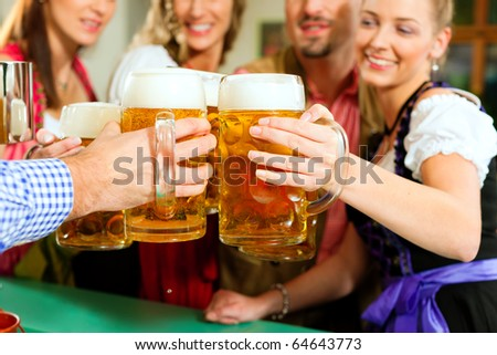 Inn or pub in Bavaria - group of young men and women in traditional Tracht drinking beer and having a party with beer - stock photo