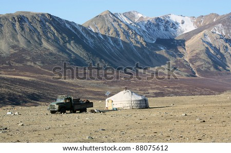 Inner Mongolia yurt in the grass land with mountain in background