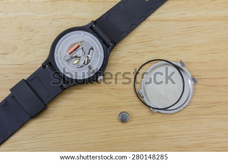 Inner parts of a wrist watch on a wooden table - stock photo