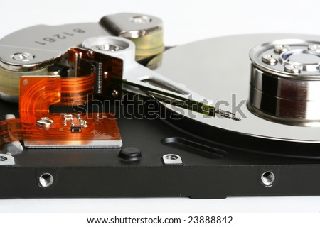 Inner workings of a hard disk, showing the disk and the magnetic head used to read and write data. - stock photo