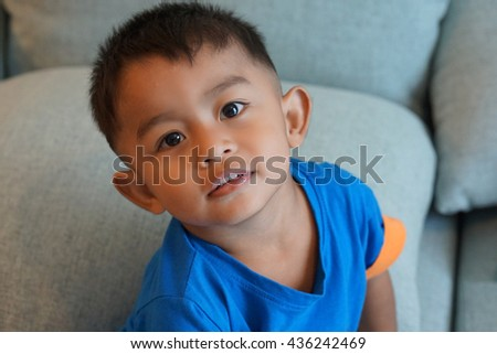 innocent smile of Thai boy while he play on sofa - stock photo