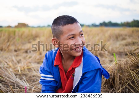 innocent smiling kid in the rural rice field. - stock photo