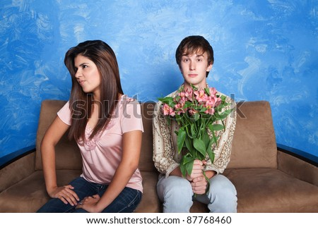 Innocent young man holds flower bouquet while his girlfriend looks away - stock photo