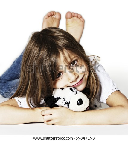 Innocently smiling girl with soft toy lying on floor in studio, isolated on white background. - stock photo