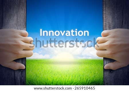 Innovation. Hands opening a wooden door then found a texts floating among new world as green grass field, Blue sky and the Sunrise. - stock photo