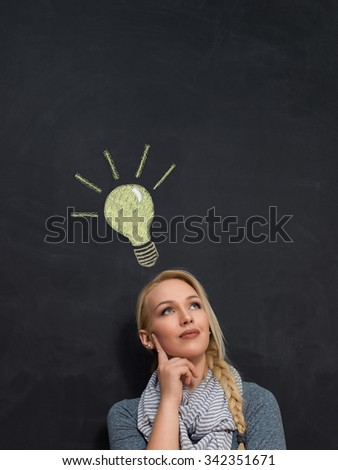 Innovative young businesswoman with a vision and bright idea standing below a shining light bulb drawn on a chalkboard - stock photo