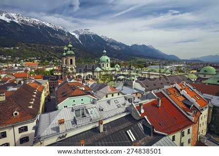 Innsbruck. Aerial view of Innsbruck from the Stadtturm, with the Innsbruck Cathedral (Cathedral of St. James ) and European Alps in the background. - stock photo