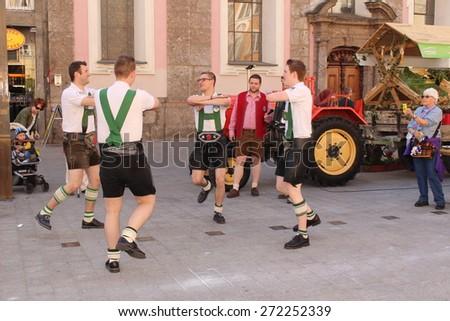 "INNSBRUCK, AUSTRIA - APRIL 24: Men are dancing in traditional Austrian leather breeches (Lederhosen) for ""Market Hall on Tour"" promotion on Maria-Theresien Street on April 24, 2015 in Innsbruck.  - stock photo"