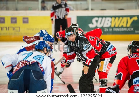 INNSBRUCK, AUSTRIA - AUG 25: Hockey game between HC Innsbruck and Medvescak Zagreb. Referee drops the puck for the opening face off, in Olympia Hall, Innsbruck, Austria on August 25, 2012. - stock photo
