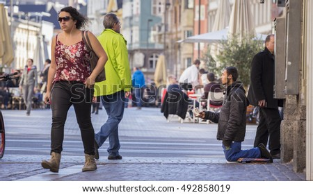 INNSBRUCK, AUSTRIA NOVEMBER 1st 2015: Refugee begging for help in the streets of Innsbruck with people walking by.