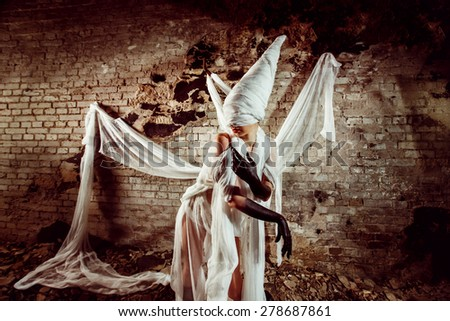 Insane evil creature in white bandage is creeping at the dark bricks wall background. Halloween concept. - stock photo