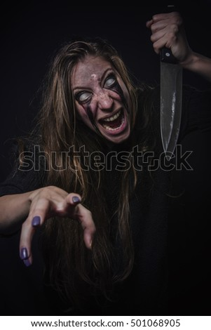 Insane horror zombie girl attacking with a kitchen knife, halloween concept, dangerous and deranged