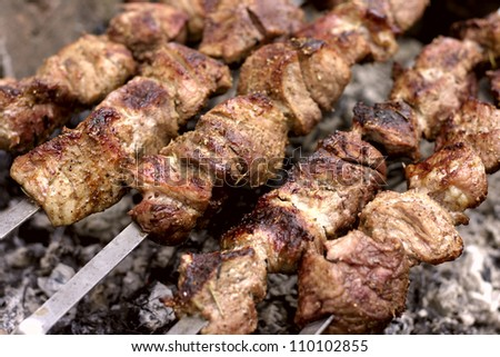 Insanely delicious kebab prepares on the fire outdoors - stock photo