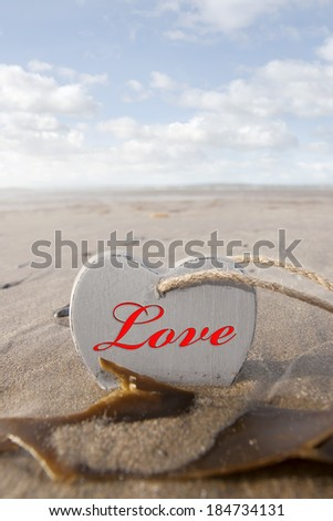 inscribed wooden love heart in the sand on a wild Atlantic way Irish beach in summer with copy space - stock photo