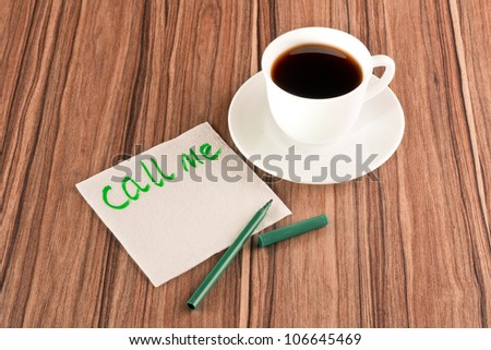 Inscription Call me on a napkin and cup of coffee - stock photo