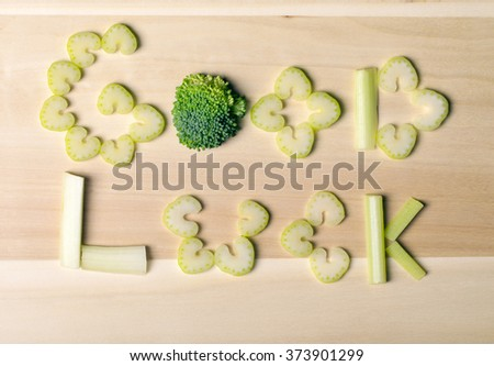 inscription good luck, text from farm products, letters from vegetables, celery, broccoli, closeup, chopped vegetables on wooden background, macro - stock photo
