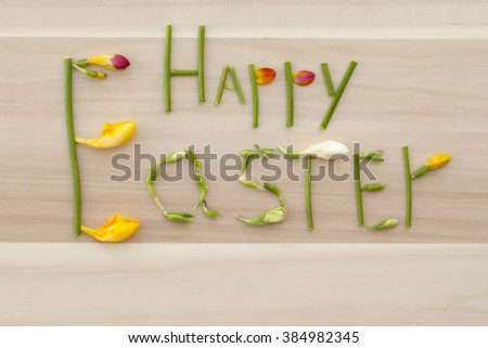 inscription Happy Easter of flowers and stems, the original lettering of the parts of flowers on a wooden Board, flat lay, text on wooden background - stock photo