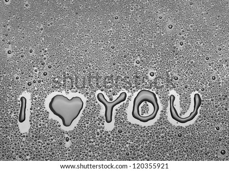 Inscription I love you written on a black background with water - stock photo