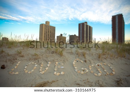 inscription Love God of seashells in the sand on the coast. East rockaway Intel. New-York. US East Coast. Tinted - stock photo