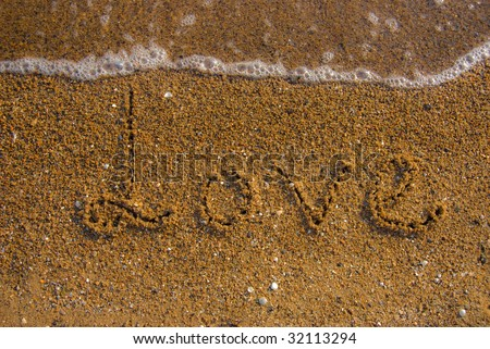 inscription love on a sand and a wave - stock photo