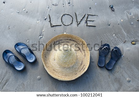 Inscription love on the sand  with a straw hat and pairs of sandals of a man and a woman. - stock photo