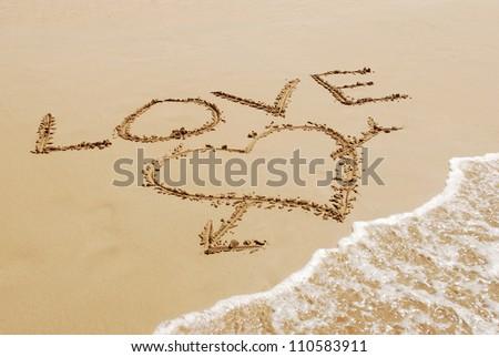 inscription love with heart on wet golden beach sand - stock photo