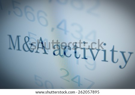 Inscription M&A (Mergers and acquisitions) activity on a PC monitor. Financial data as background. Multiple exposure. - stock photo