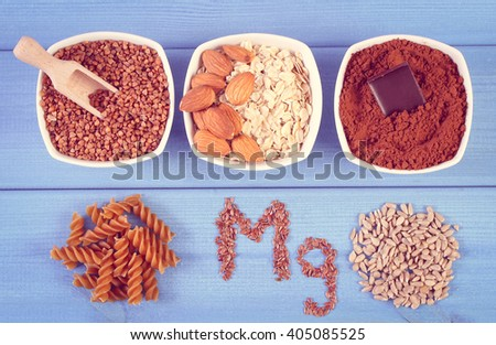 Inscription Mg, ingredients and products containing magnesium and dietary fiber, healthy nutrition, wholemeal pasta, sunflower, buckwheat, oatmeal, linseed, almonds, chocolate, powdery cocoa - stock photo