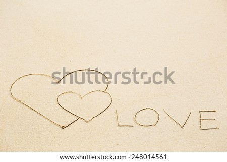 Inscription of Love with two hearts on wet beach sand. Concept of celebrating the St. Valentine's day at some exotic place - stock photo
