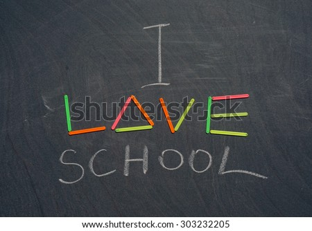 "inscription on blackboard with chalk and counting sticks ""I love school"""