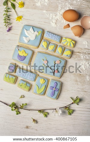 inscription on Easter cookies and festive motif on the background of a wooden table - stock photo