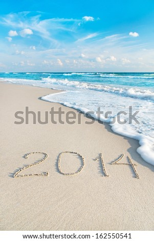 inscription 2014 on sea sand beach with the sun rays against wave foam and sky - vacation concept - stock photo